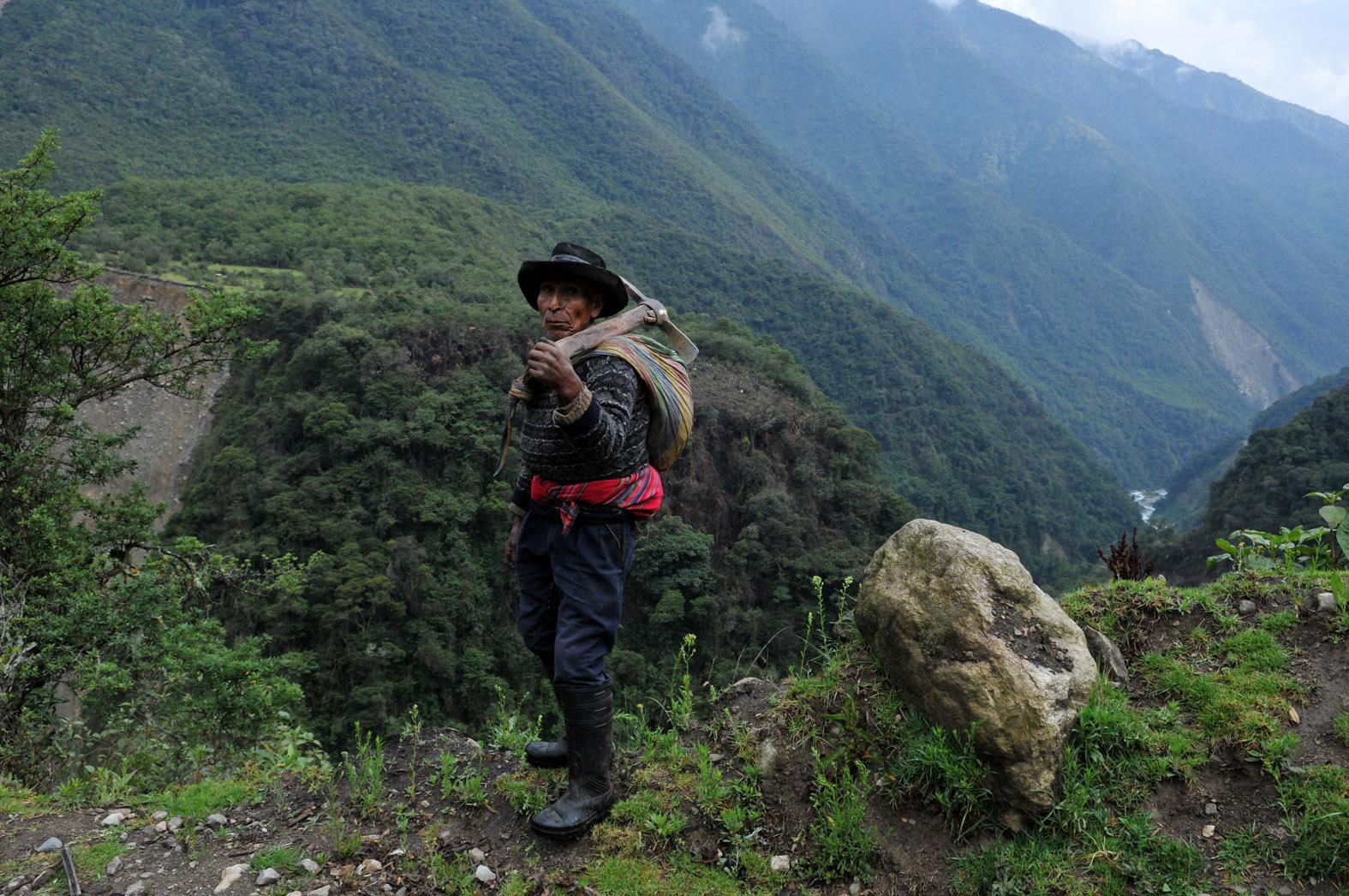 foto van man in Salkantaygebergte met bijl en zak op rug