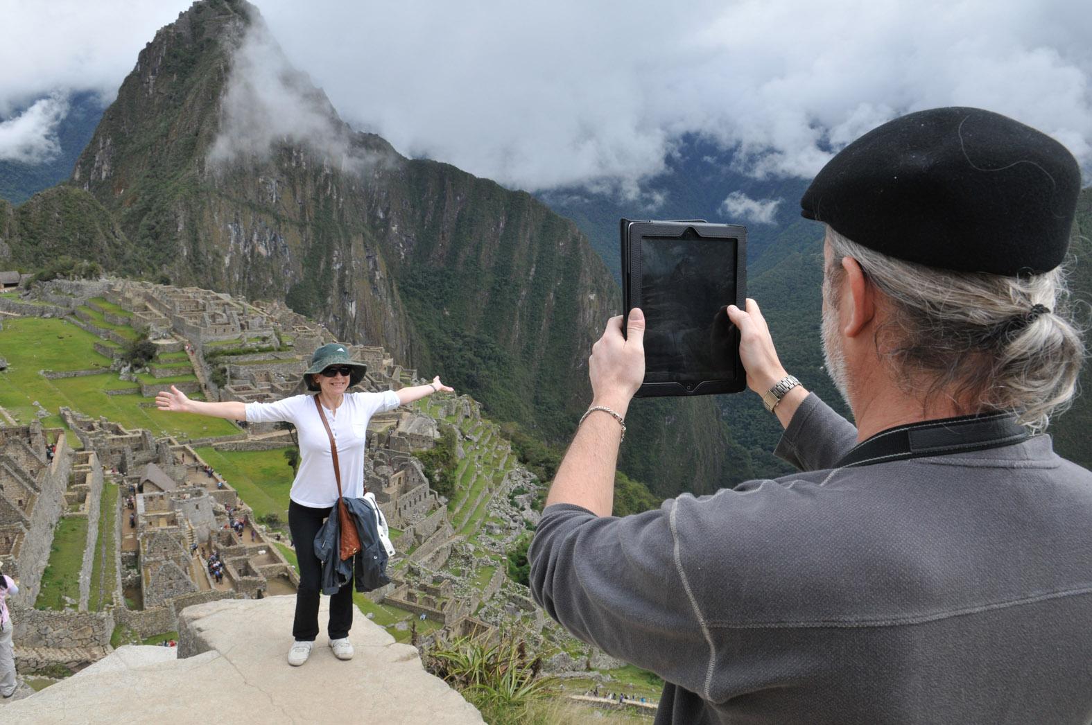 Salkantaygebergte met vrouw op rots en man die foto van haar maakt met iPad