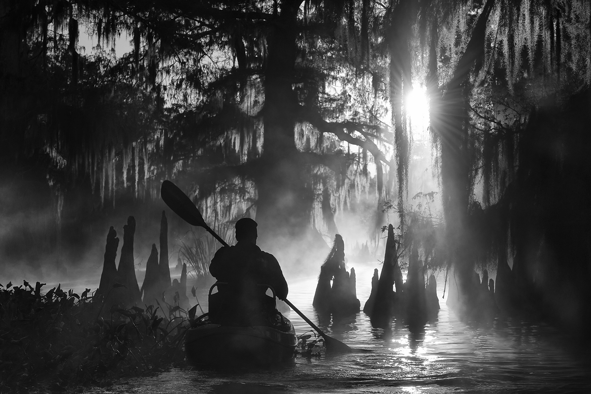 foto van man in kano in oerwoud zwart wit als silhouet