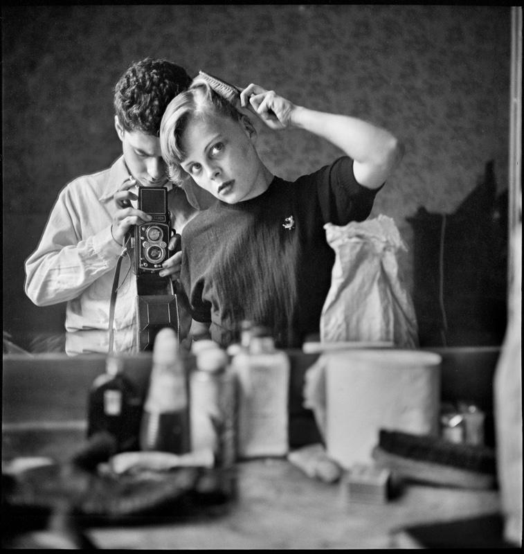zwartwit foto van Elliott Erwitt van vrouw die haar kamt in spiegel en fotograaf die erachter staat met camera