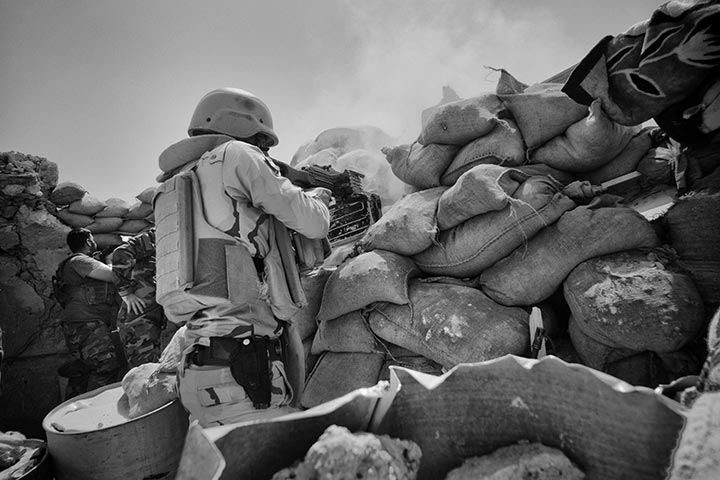 foto: Winnaar Zilveren Camera 2015: Eddy van Wessel | man met geweer achter blokkade me zandzakken in Sinjar