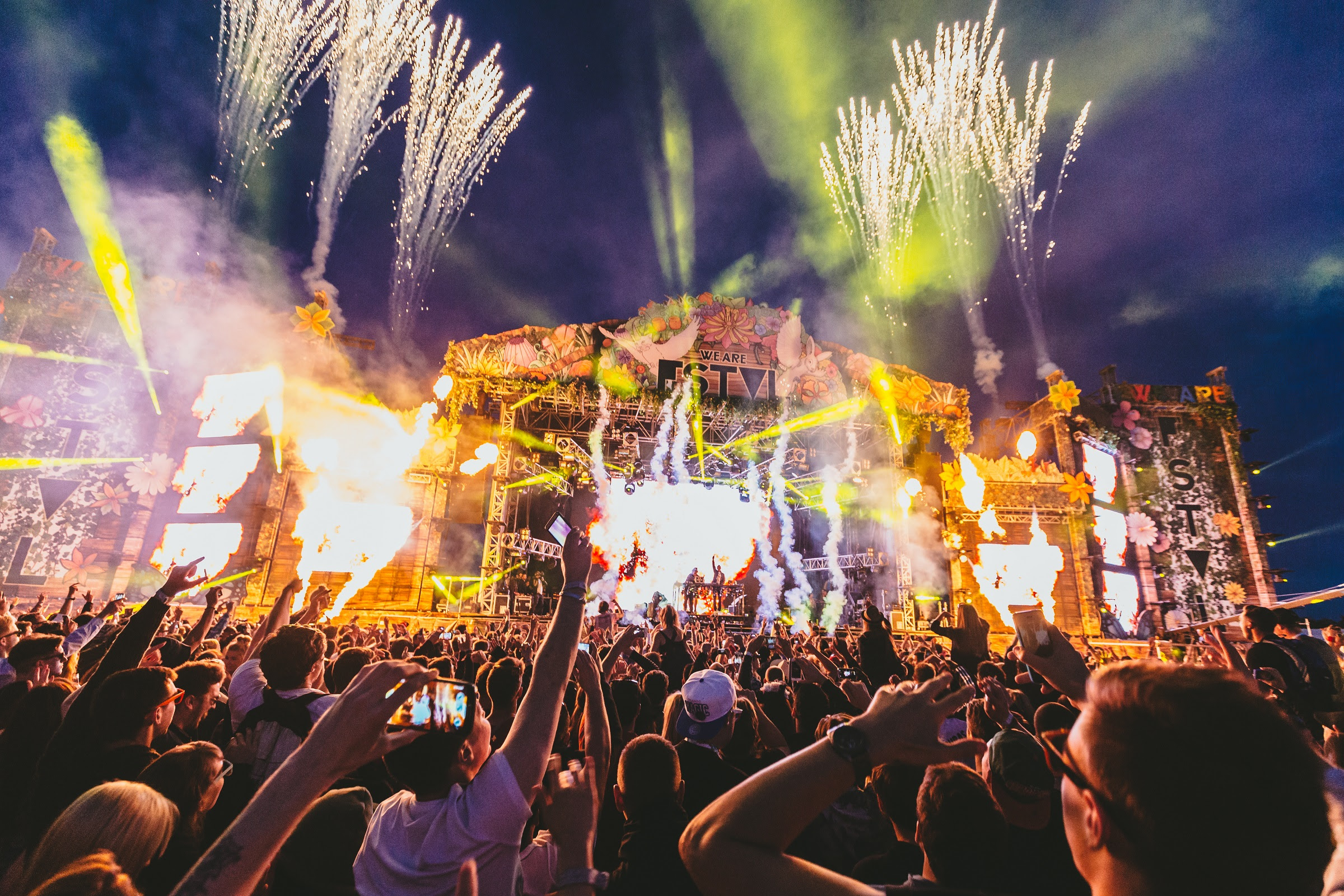 foto van podium met band en publiek ervoor in de nacht
