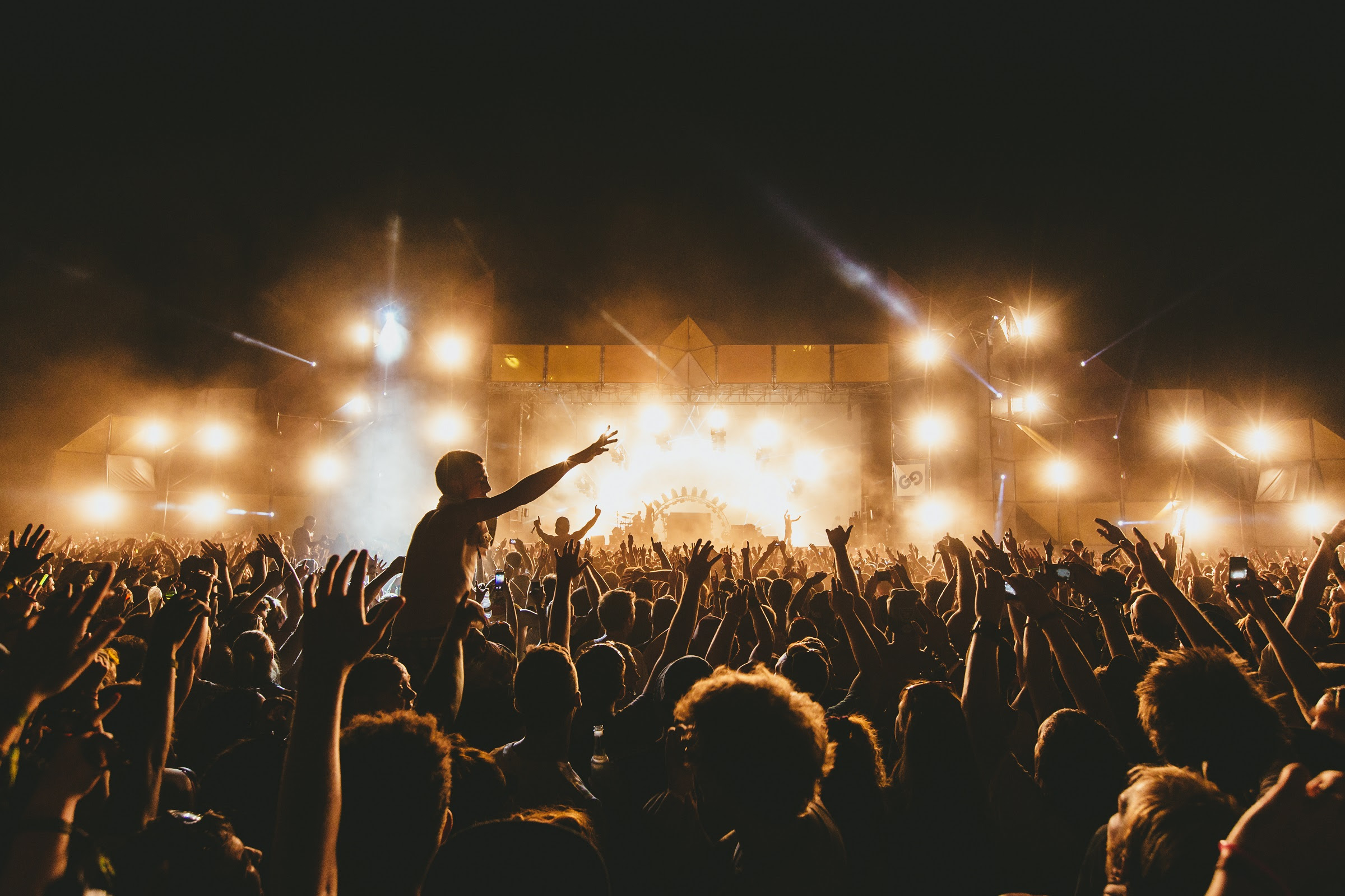 foto: © Paul Underhill van publiek met handen in lucht bij podium festival in nacht