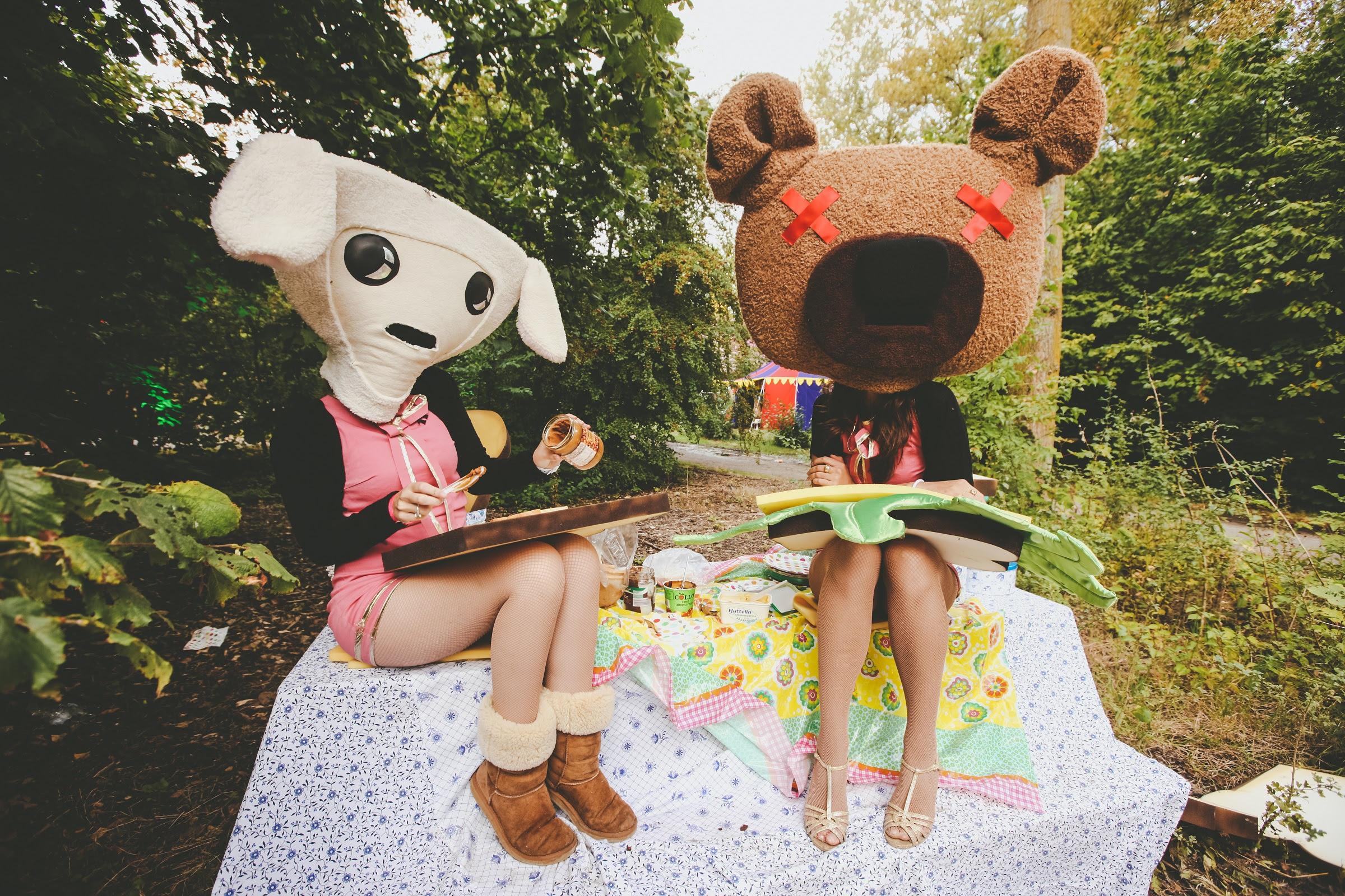 foto: © Paul Underhill van twee dames verkleed als beer en schaap op steen zittend