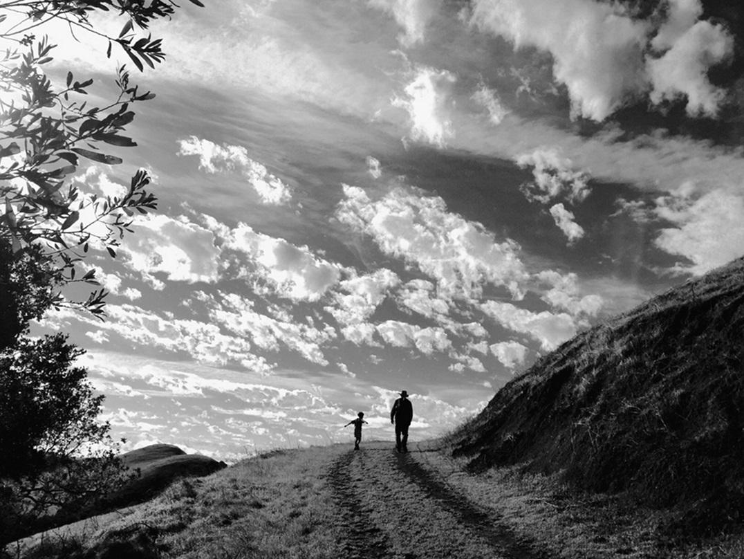 fzwartwi toto van een man en een kind lopend op een heuvel met mooie lucht van wolken