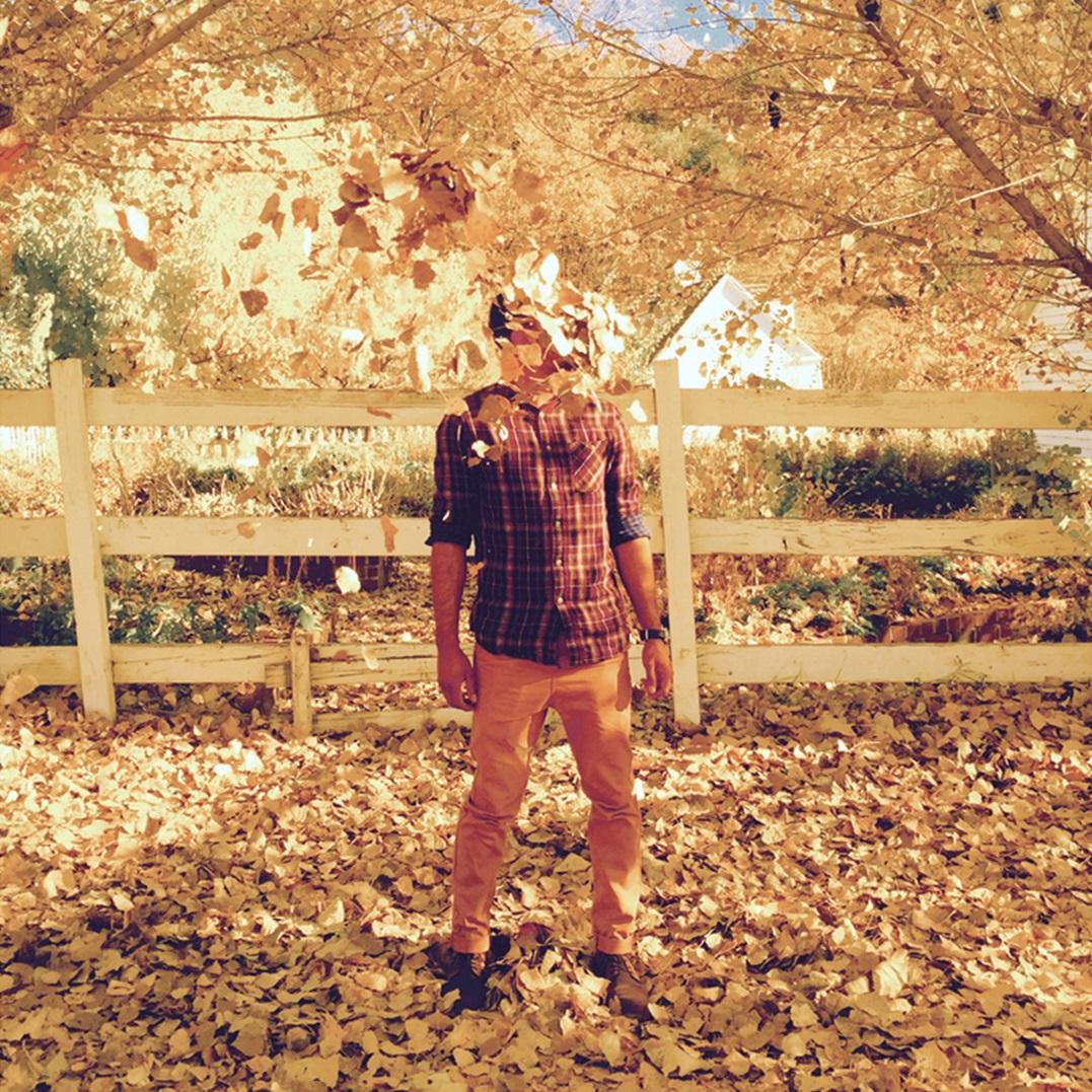 foto van man in herfst tuin met hoge hekken en met hoofd van bladeren