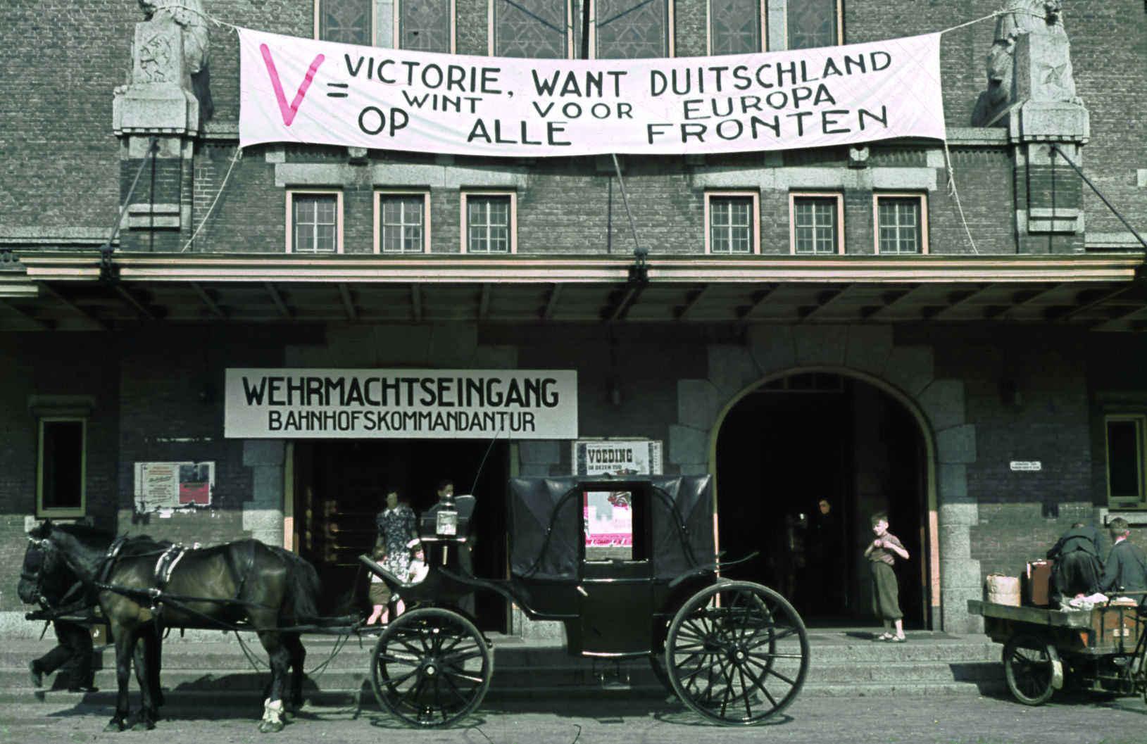 foto: Alphons Hustinx | Maastricht 194, koets met paarden voor station met spandoeken van de nazi';s