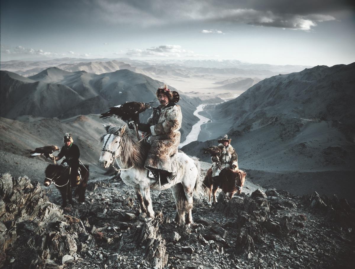 foto van drie mannen op paarden met roofvogels in handen op gebergte Kazakhs, Mongolia