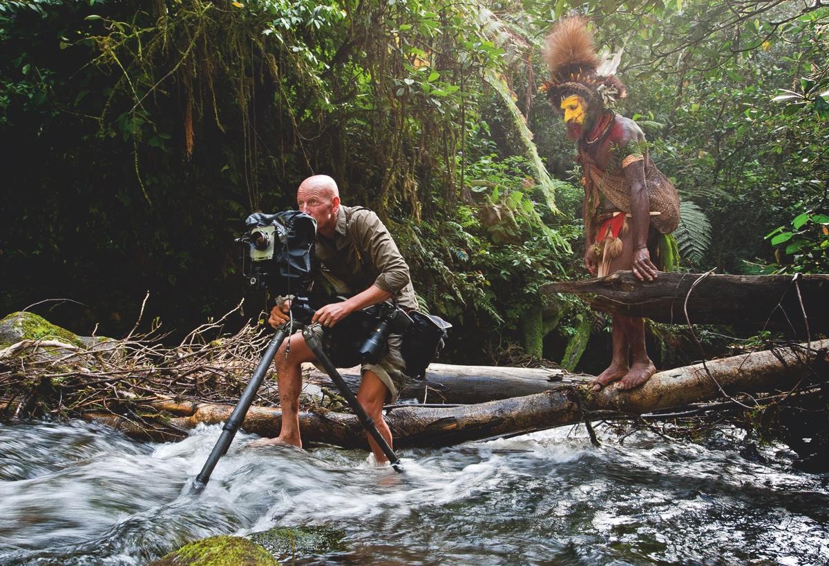 foto van Jimmy Nelson aan het werk met camera in water in oerwoud