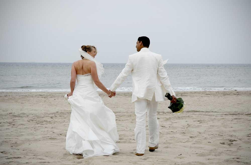 trouwfoto van echtpaar in wit op het strand hand in hand lopend naar de zee