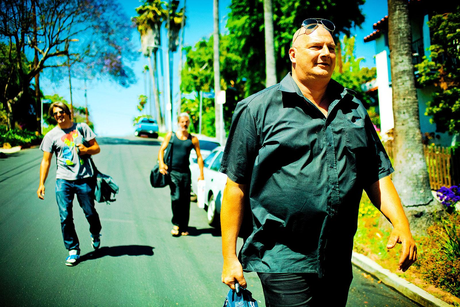 foto van drie mensen die op straat lopen in een zonnig land, een dikke man voorop en jongen links erachter en een andere man iets verder naar achter