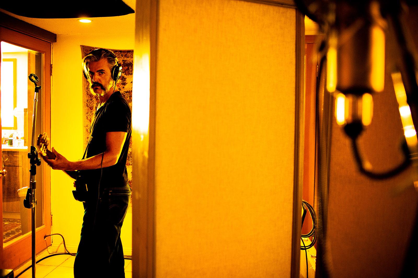 foto van een man met elektrisch gitaar en koptelefoon op in een kamer die gelig verlicht is
