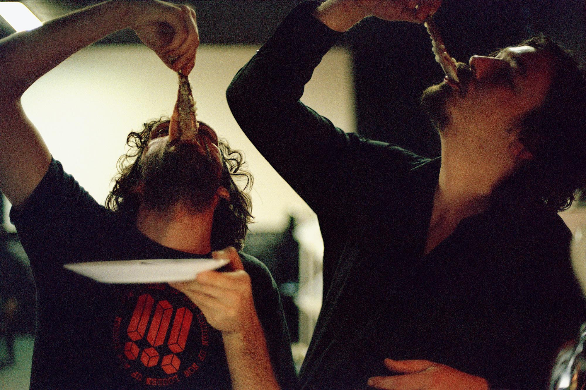 foto van twee mannen die haring eten en deze heel in mond hangen, foto: Annie Hoogendoorn | Daan & Bjorn eating haring (zZz), LVC Leiden, dec 2005