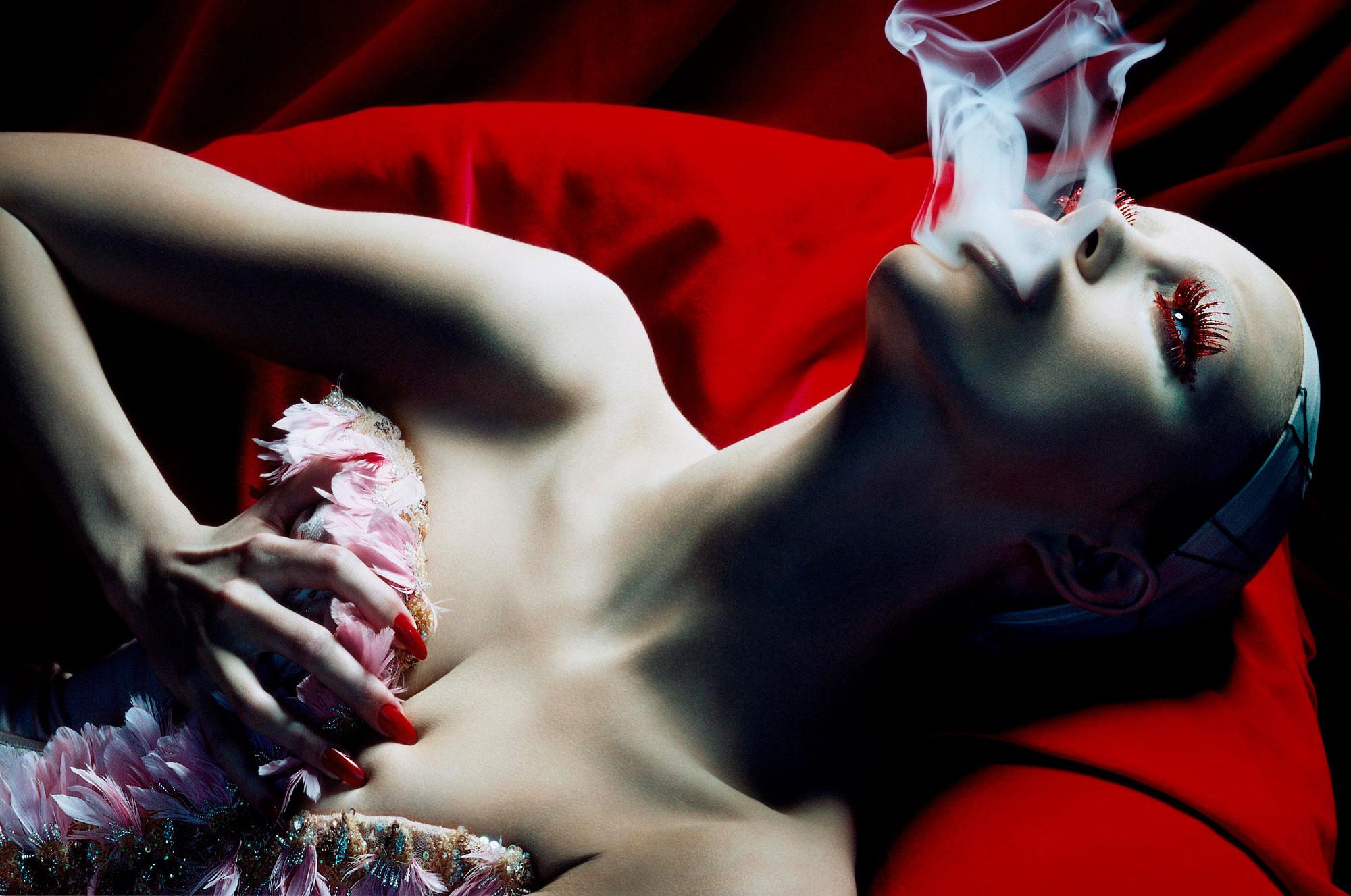 foto van vrouw vanaf middel liggend en rook uitblazend