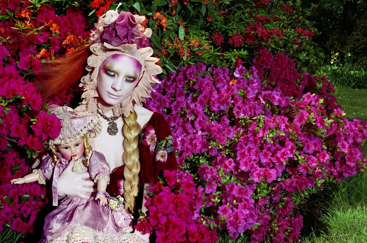 foto van Miles Aldridge van vrouw tussen bloemenstruiken met blonde vlecht en pop in arm en hoed van bloemen