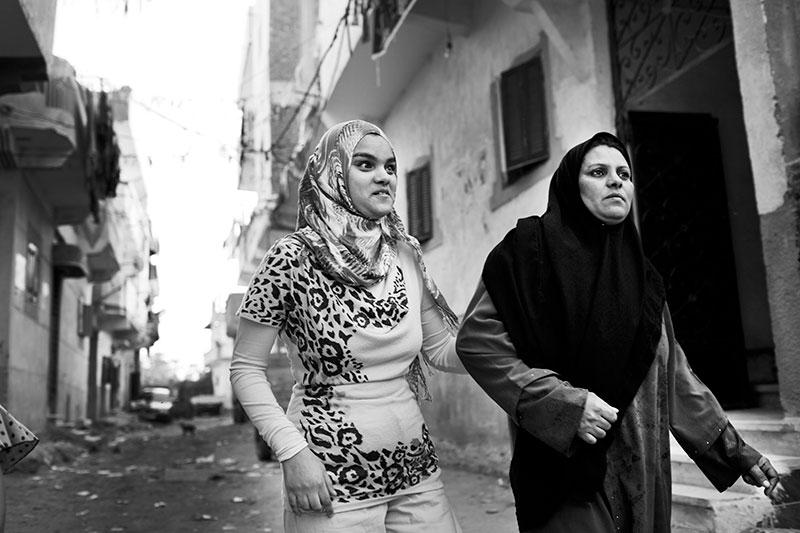 foto: Ahmed Hayman, Egypt, ftwee vrouwen met hoofddoek in steeg gearmd lopend, de ene is de dochter die blind is en houdt de moeder vast