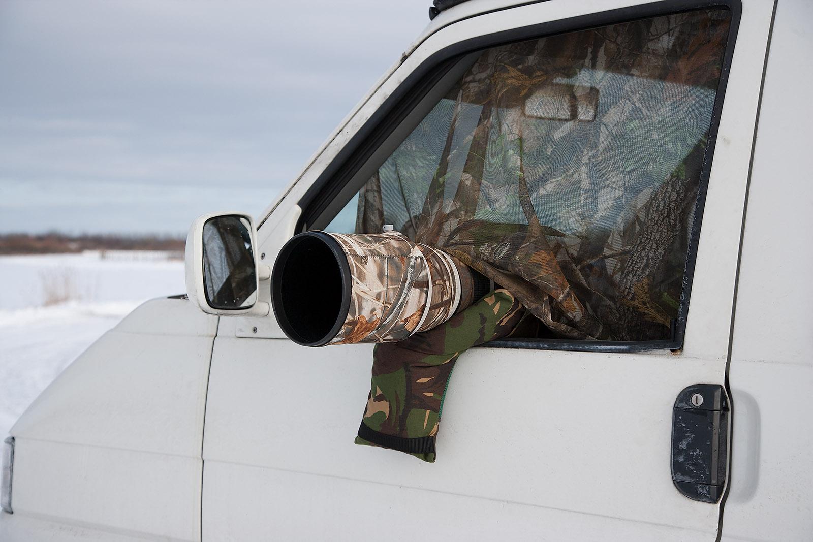 foto van wit busje met camouflagedoek voor het raam en een cameralens die uit voorraam steekt ook gecamoufleerd