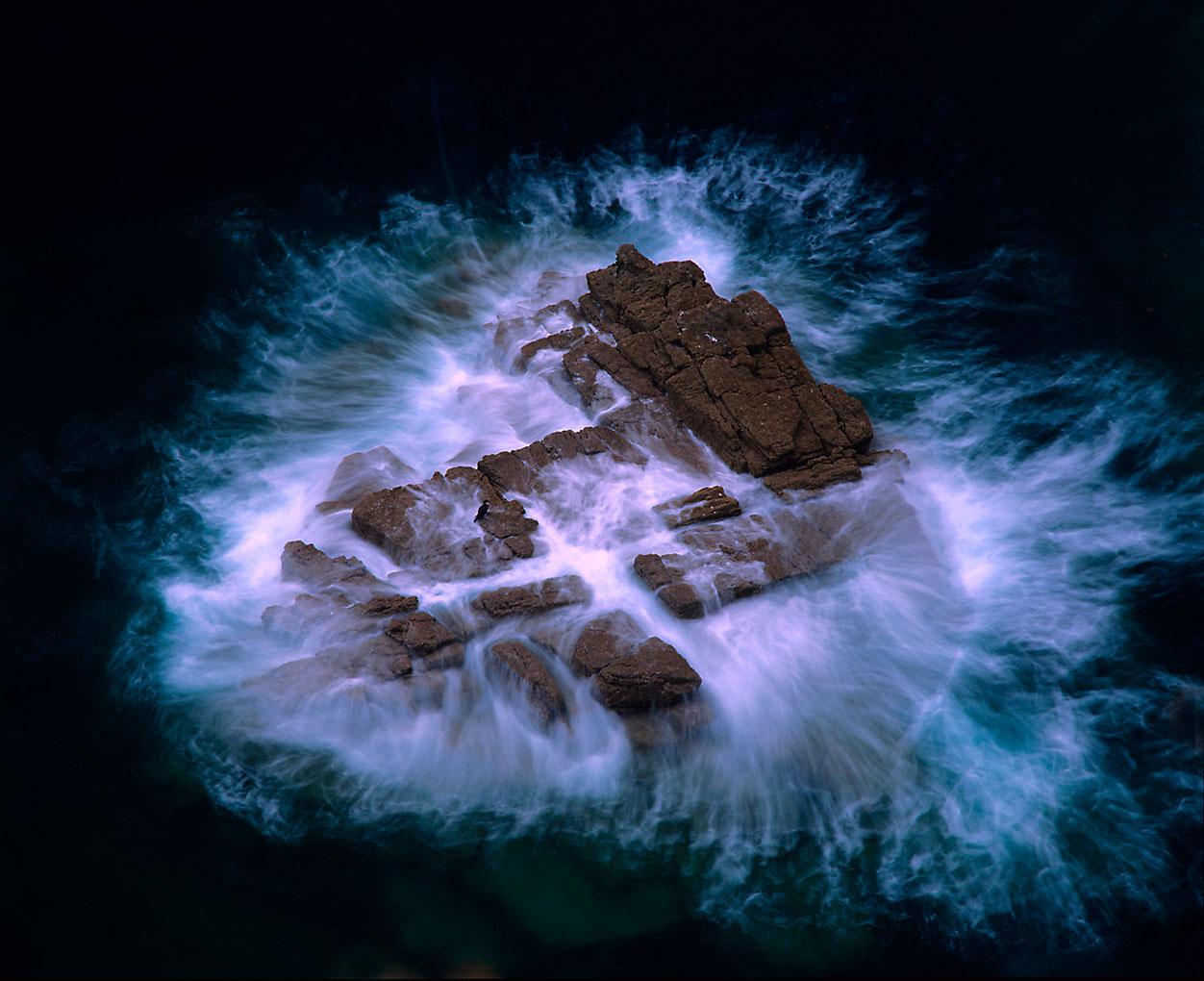 Door Ruben Smit - een rots bij Britanie waar een kuifaalscholver bijna wordt overspoeld door het opkomende tij
