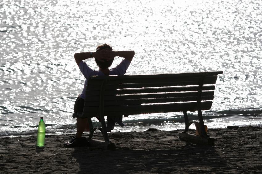 tegenlicht foto, vrouw op bank bij water reflectie en groene fles op de grond