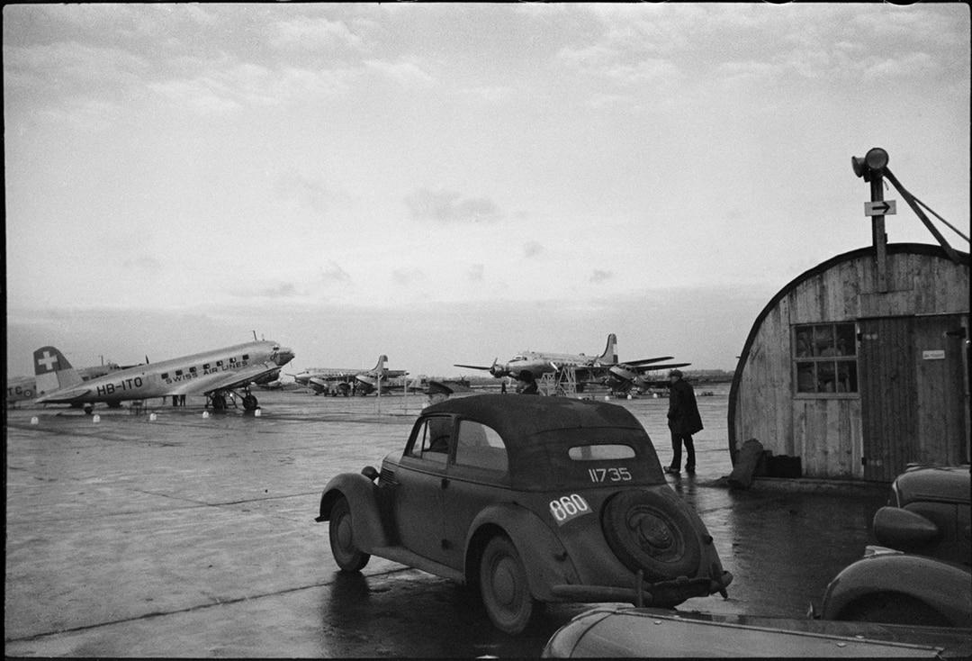 foto van werner bischof van een vliegtuigbasis in zwartwit met een deux cheveaux op voorgrond