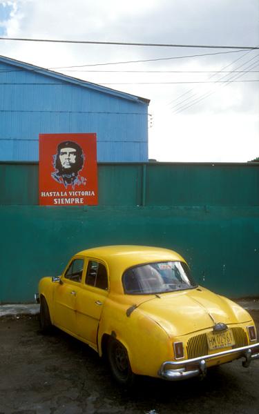 Polychroom kleurgebruik met felle drukke kleurvlakken:| gele cubaanse auto bij schutting met rood affiche