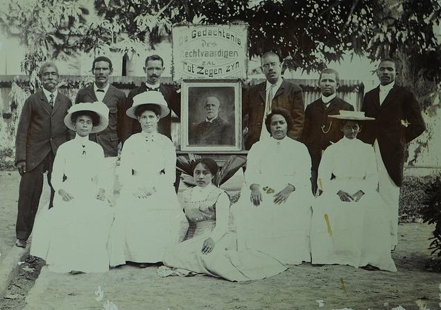 Deze foto komt uit de collectie van het Stichting Surinaams Museum en is gedigitaliseerd in samenwerking met het Nationaal Historisch Museum, Leden van de Free Evangelical Church met een portret van Reverend Meyer Salomon Bromet.