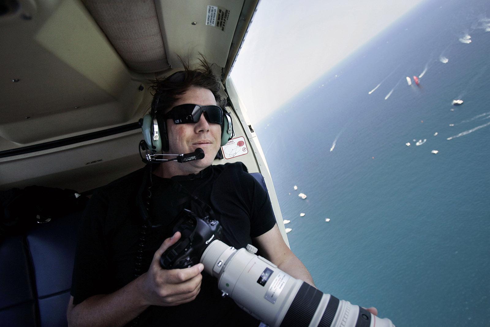 Jasper Juinen met camera en lange lens in de lucht bij open deur vliegtuig