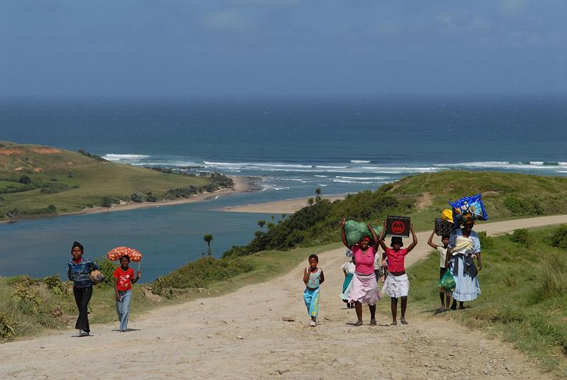 Zuid-Afrika - Wild Coast, vrouwen en kinderen lopen langs kust met goederen op hoofd