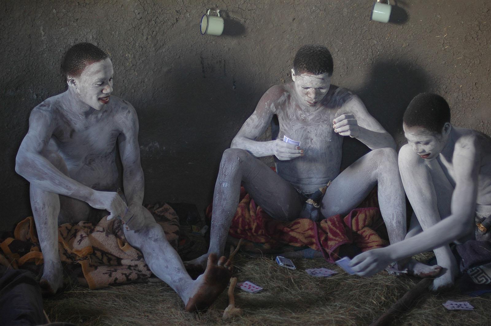 Fotografie Zuid-Afrika - Wild Coast, zwarte mannen wit geschminkt spelen kaart in hut op de grond zittend