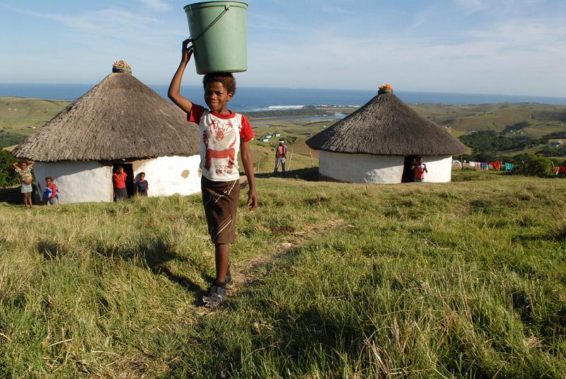 foto: Tom van der Leij zuid afrika, jongen met emmer op hoofd op heuvels bij zee, west coast