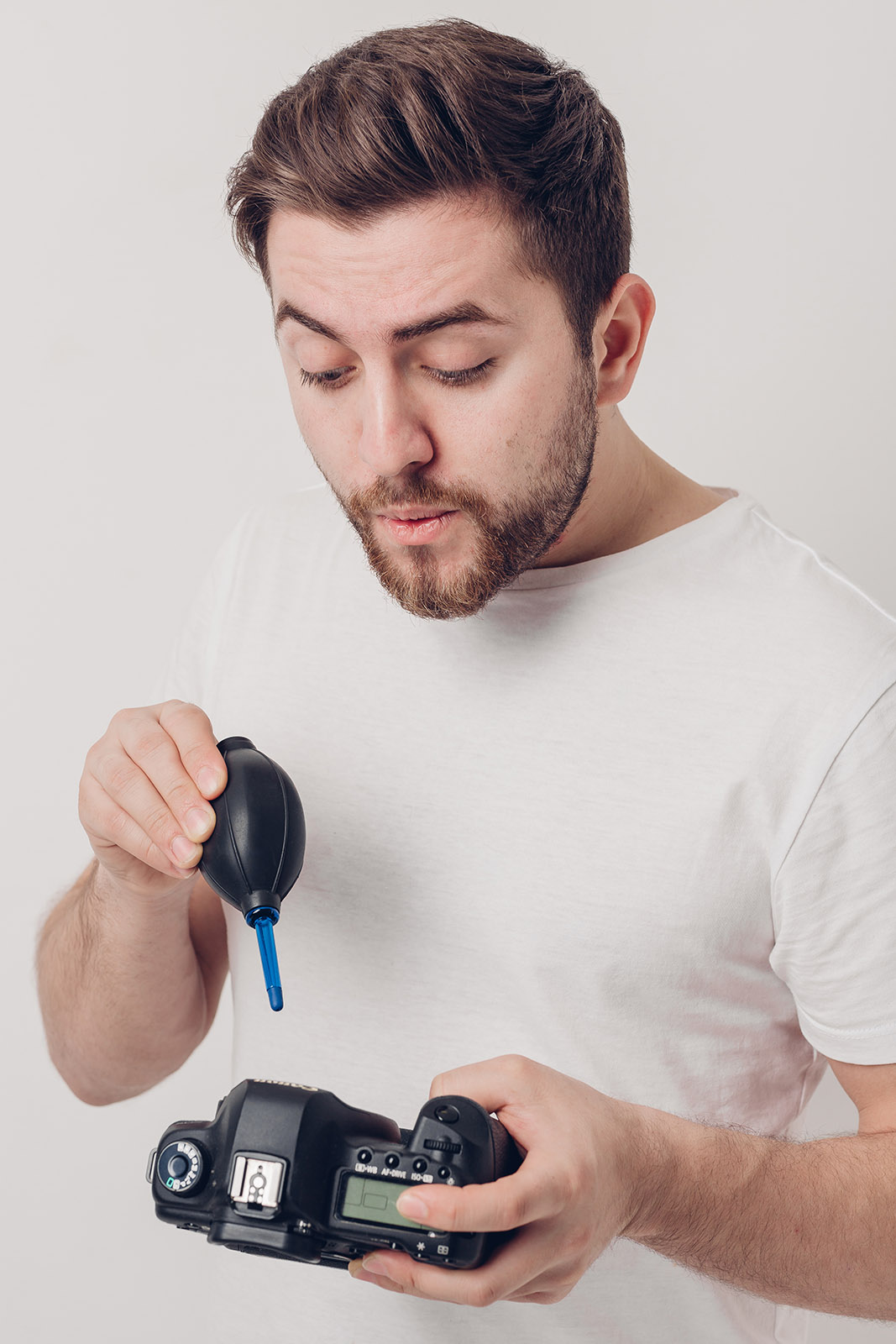 foto van man die camera schoonmaakt met luchtspuiter en zelf ook blaastt