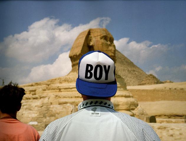 foto van Martin Parr - man met petje met tekst 'boy' bij Egyptische sphinx