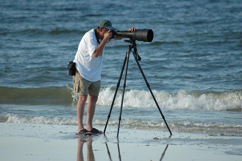 man met camera en telelens op statief bij branding zee
