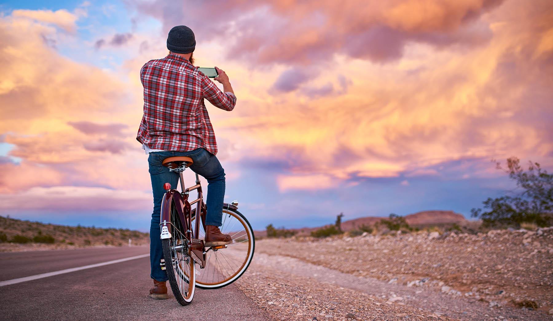 man op fiets maakt foto met mobiel van mooie lucht