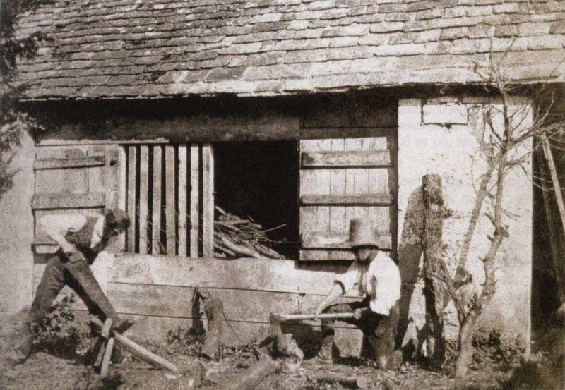 oude foto sepia schuur met twee mannen die hout zagen