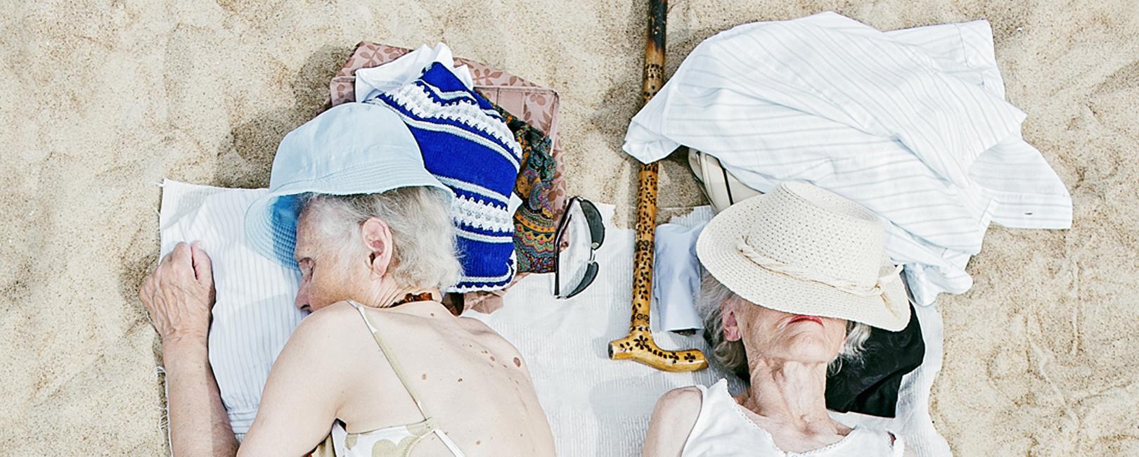 foto van Tadao Cern, twee oudjes slapen op badlaken op zand
