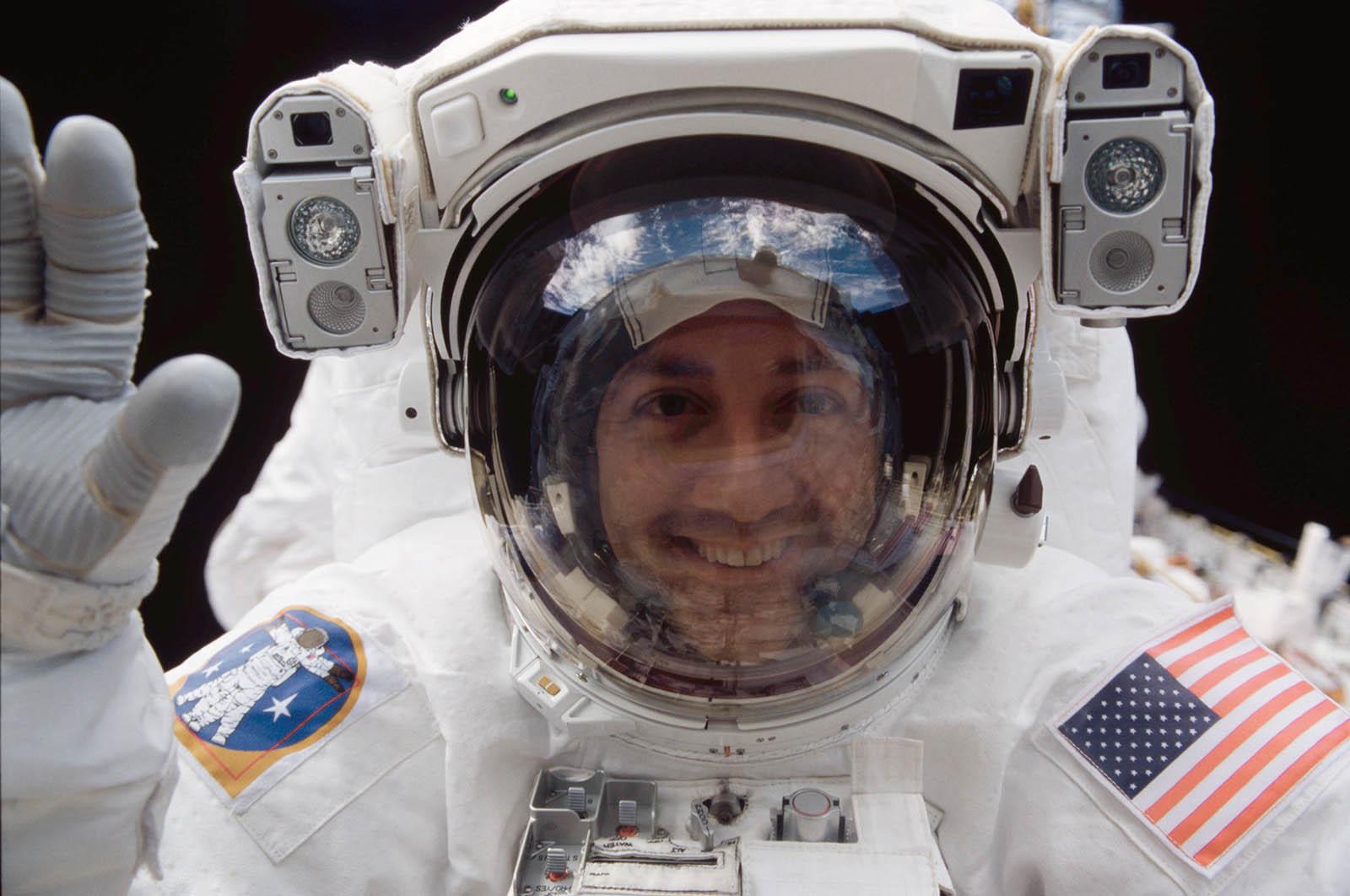 Astronaut Michael Massimino groet vanuit de ruimte zijn collega's in spaceshuttle Columbia (2002).