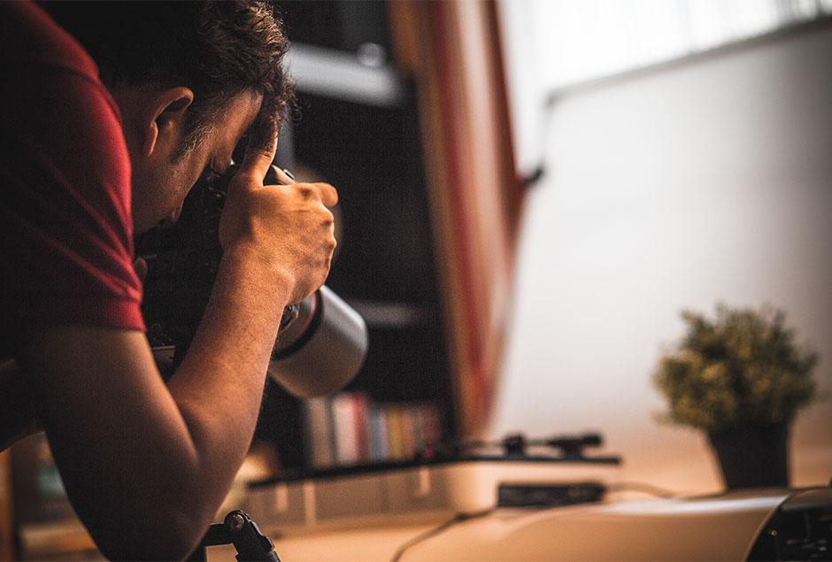 man maakt foto met camera met lange lens van zijn bureau
