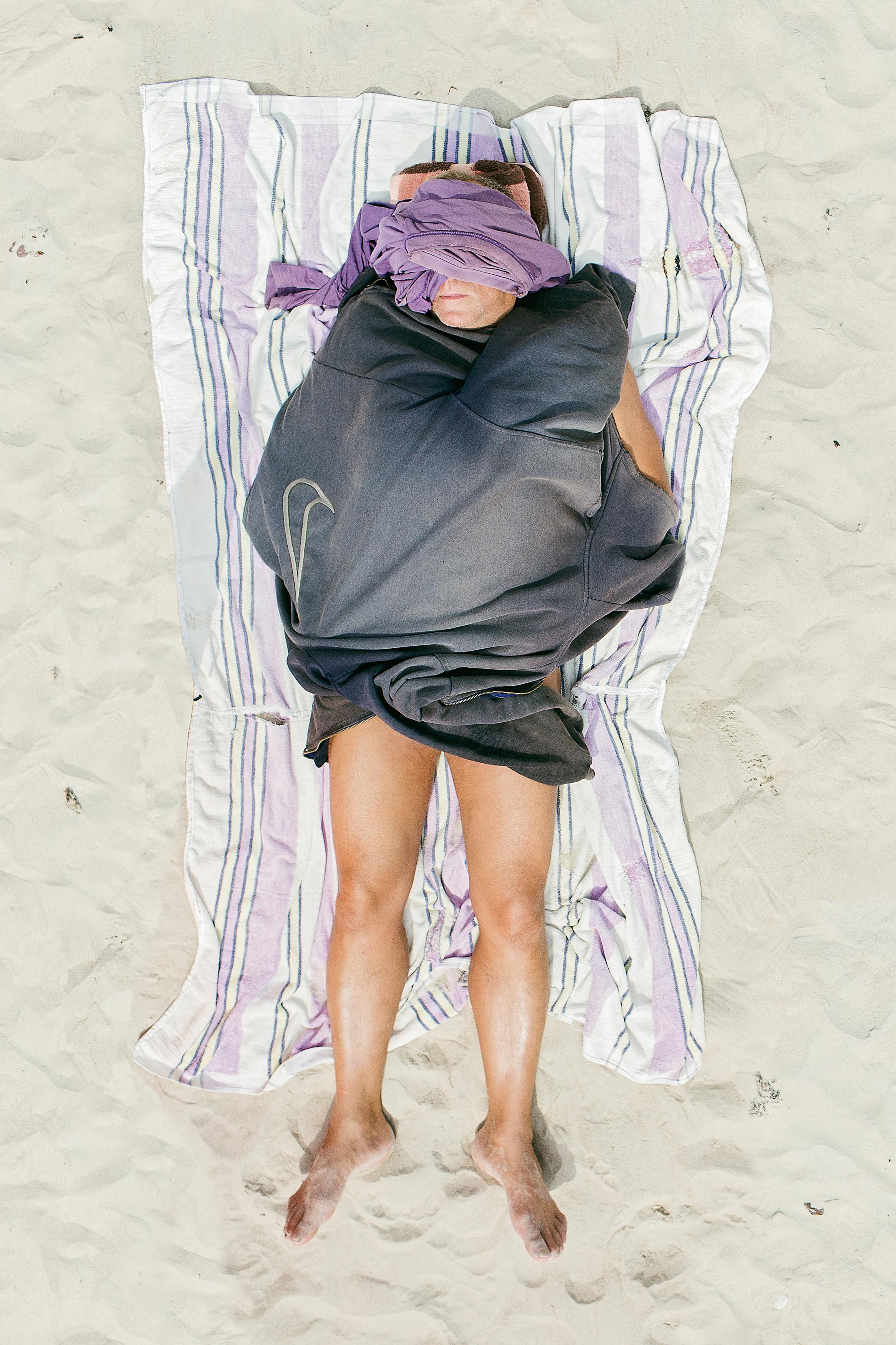 man op strandlaken op zand
