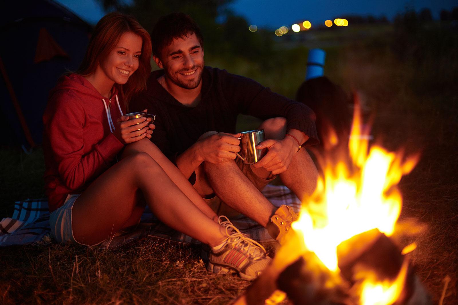 man en vrouw bij kampvuur in avond