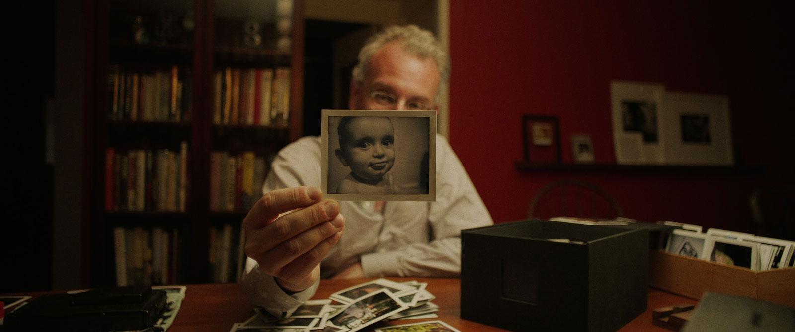 man met berg polaroids toont een polaroidfoto van baby