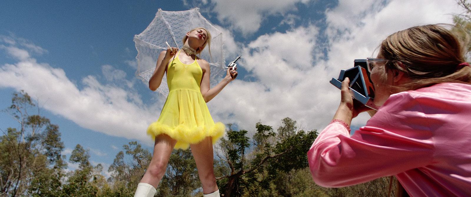 vrouw maakt polaroid foto van meisje in geel jurkje