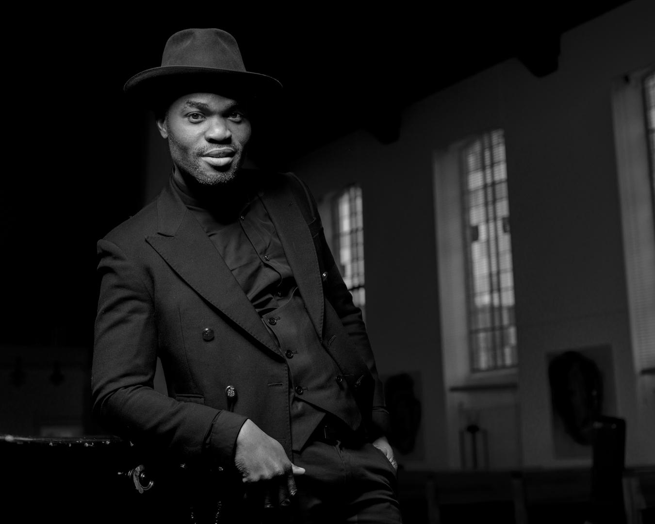 foto: ©Ferry Knijn - zwarte man in pak in gebouw met hoge ramen