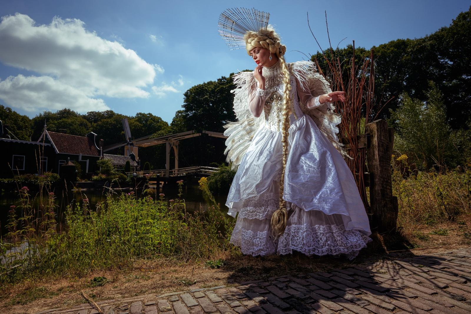 foto: © Frank Doorhof - model met witte jurk en veren op pad bij brug en huisjes