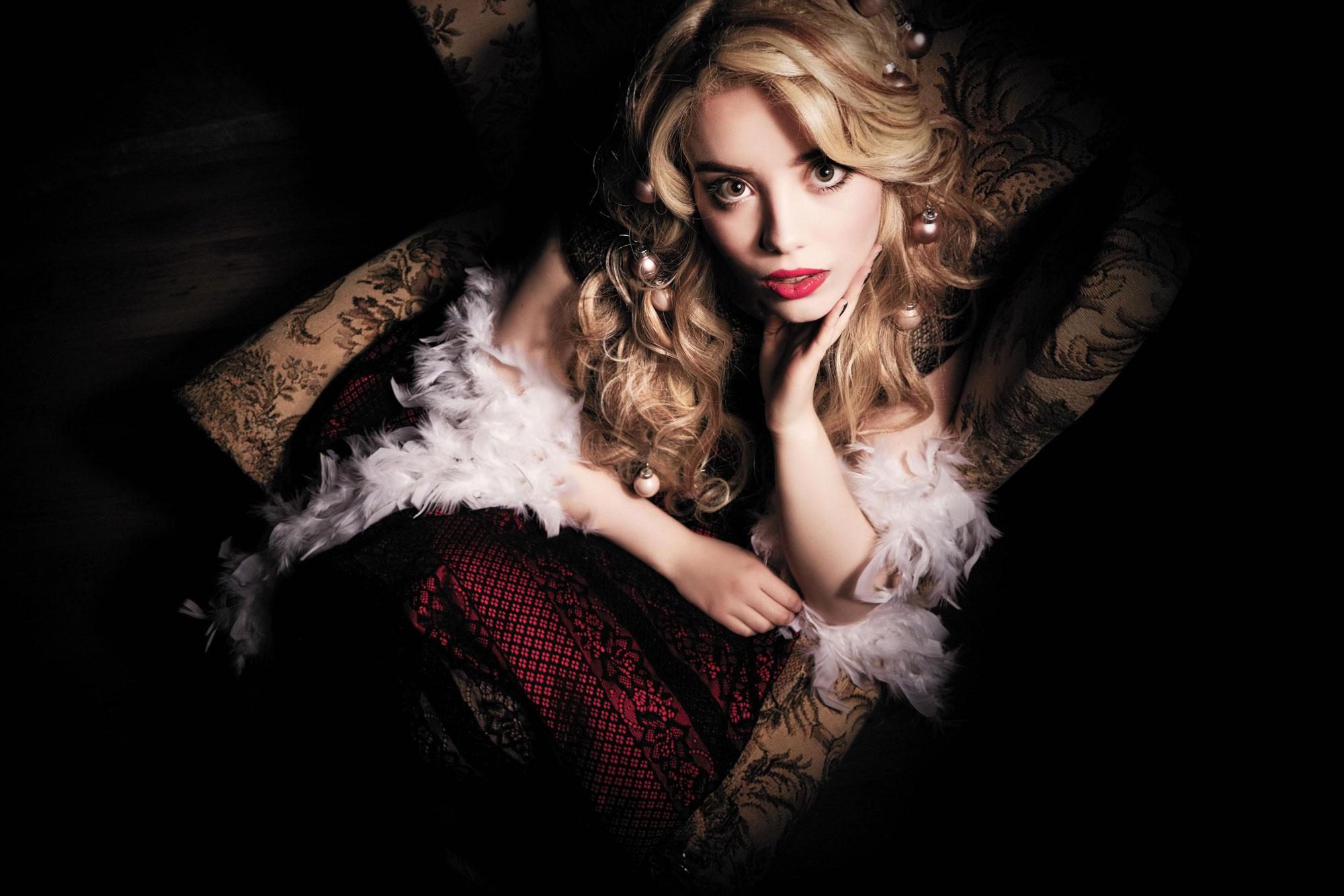 foto: © Frank Doorhof - model met blonde krullen kerstballen in haar en witte veren op bed