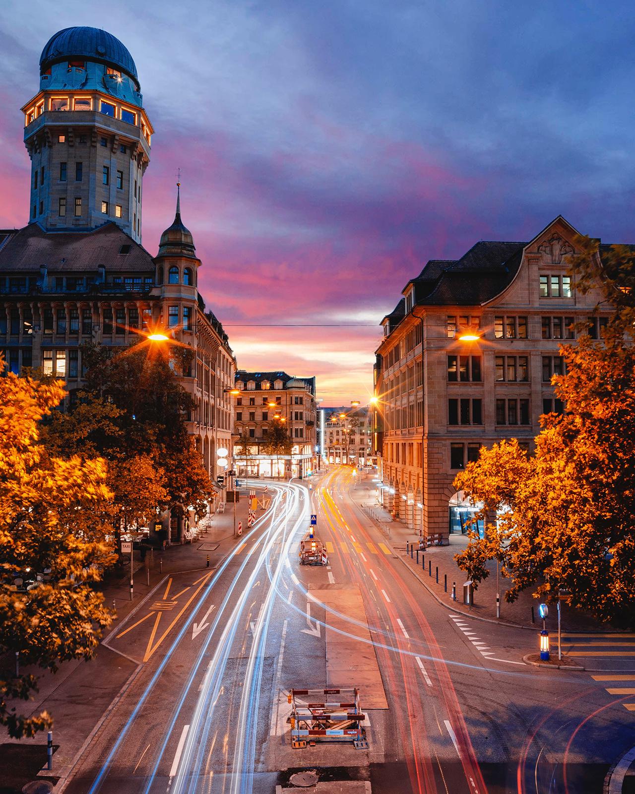 straat in stad met schemerlicht en strepen van verkeer vanaf hoog punt gefotografeerd