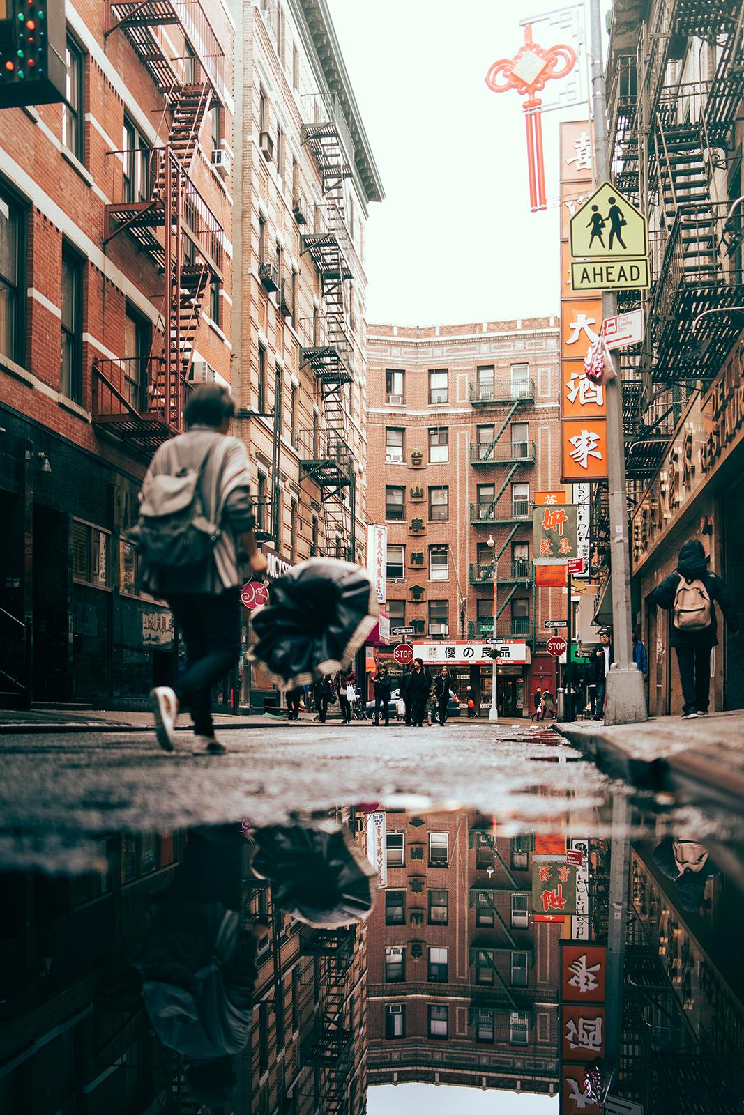 straat in stad met hoge gebouwen met mensen en reflecties in plas