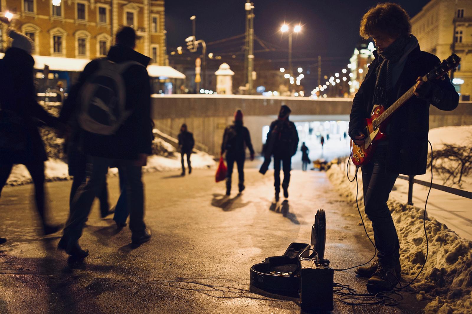 straat in stad met mensen en muzikant bij avond