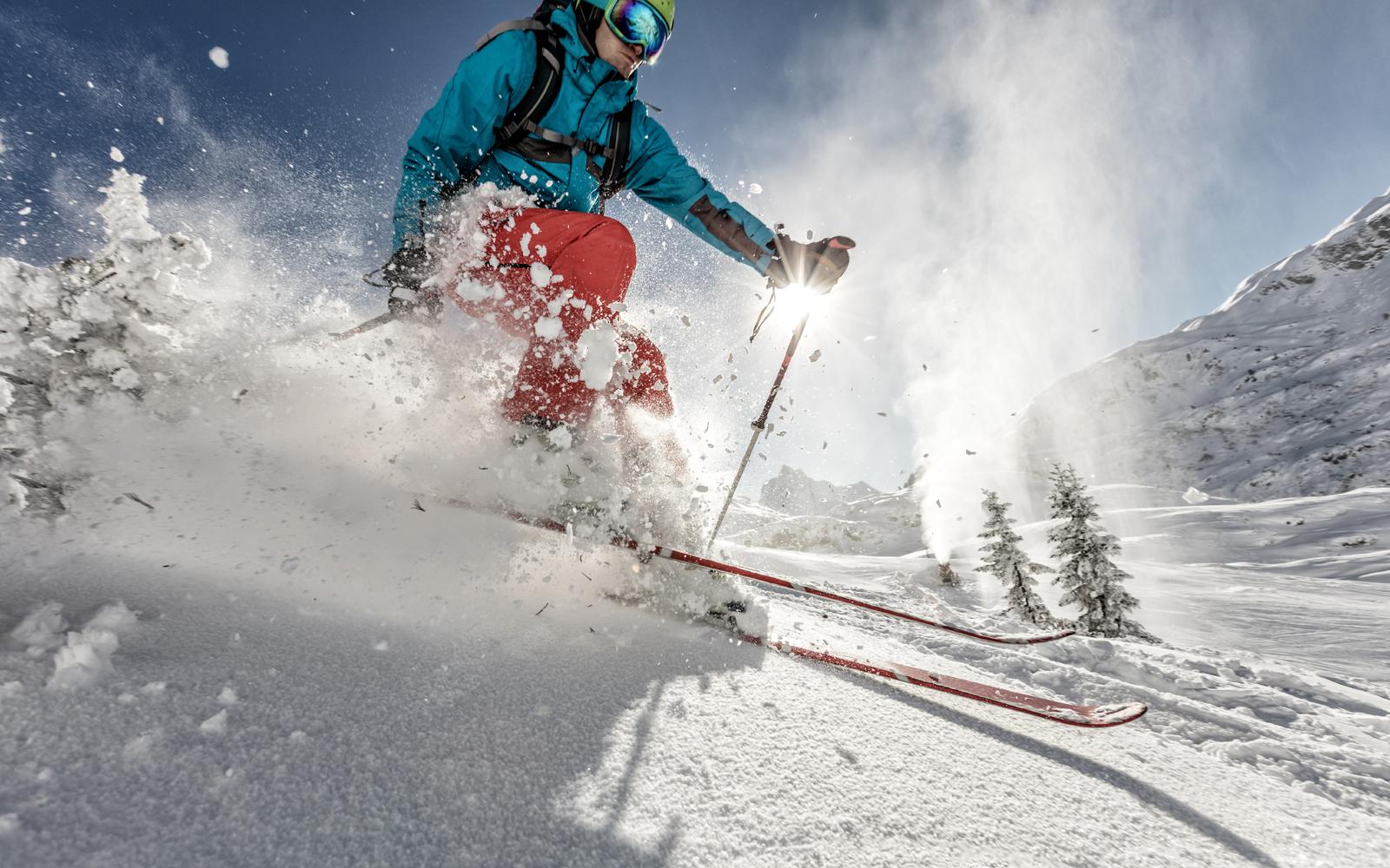 skier gaat van heuvel af in sneeuw