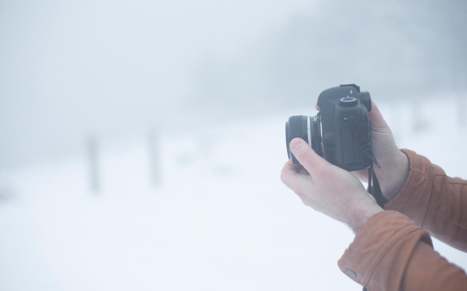 handen die camera vasthouden in sneeuw omgeving
